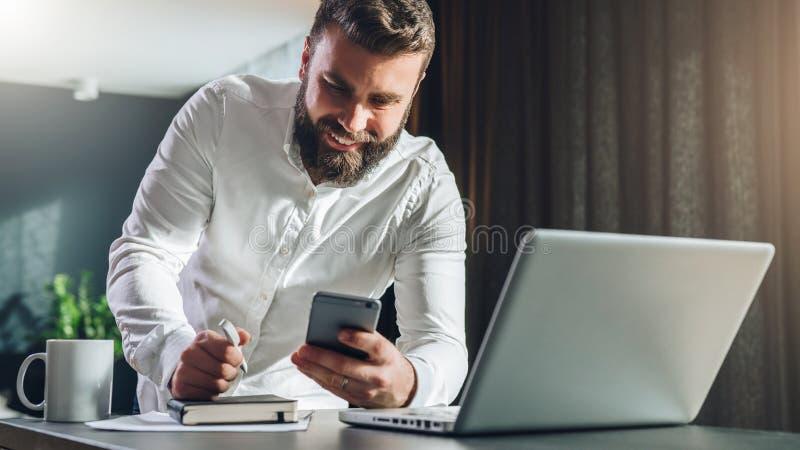 Giovani che smilling uomo d'affari barbuto che sta tavola vicina davanti al computer portatile, facendo uso dello smartphone L'uo fotografia stock