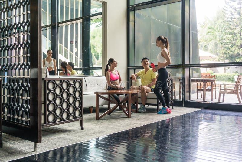 Giovani che socializzano nell'area del salotto di un club di salute d'avanguardia immagine stock