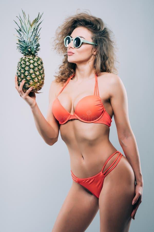 Giovani che sorridono ragazza abbastanza sexy in occhiali da sole che tengono ananas con il corpo del porfect isolato sui precede fotografia stock libera da diritti