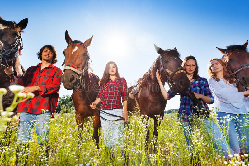 Giovani che stanno in una fila con i loro cavalli fotografia stock libera da diritti