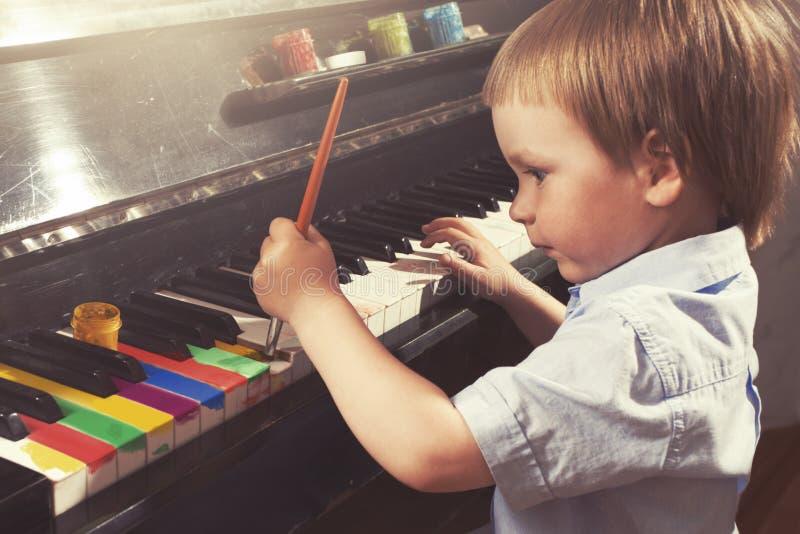 Giovani chiavi del piano della pittura del ragazzo Belle arti e musica immagine stock