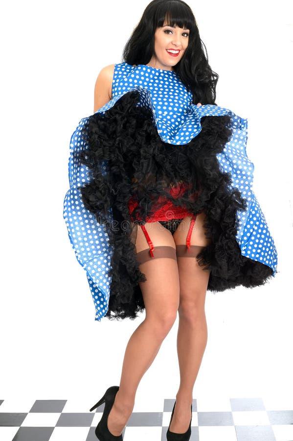Giovani cinghia e calze di bretella rosse d'annata affascinanti sexy trasandate di Pin Up Model Posing In fotografie stock libere da diritti