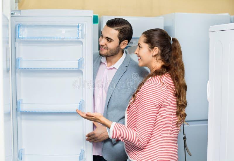 Giovani clienti soddisfatti che esaminano i grandi frigoriferi fotografie stock