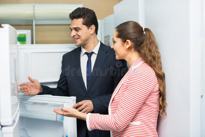 Giovani clienti soddisfatti che esaminano i grandi frigoriferi immagini stock