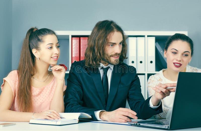 Giovani colleghe che lavorano insieme in uno studio coworking moderno Soci commerciali che per mezzo del computer portatile e dis fotografia stock