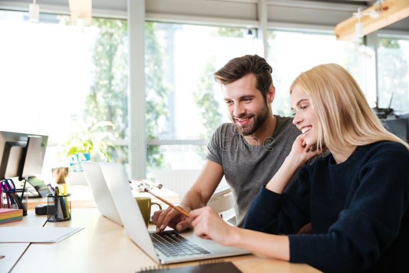 Giovani colleghi felici che si siedono nell'ufficio che coworking facendo uso del computer portatile immagine stock
