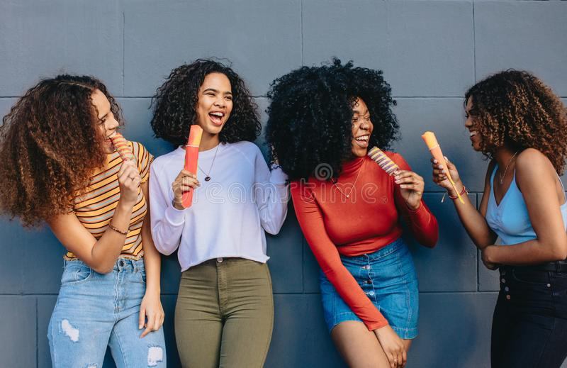 Giovani compagni che mangiano il gelato fotografie stock