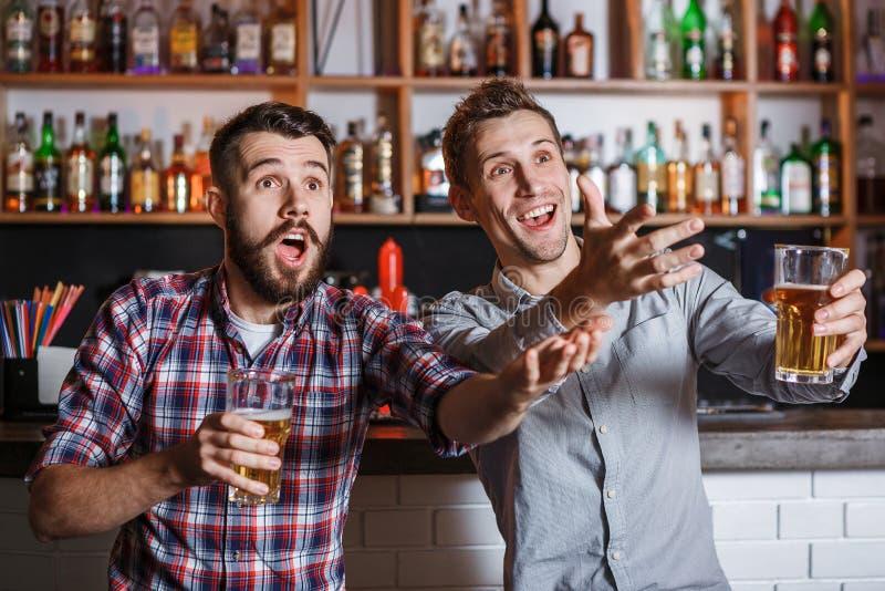 Giovani con calcio di sorveglianza della birra in una barra immagini stock