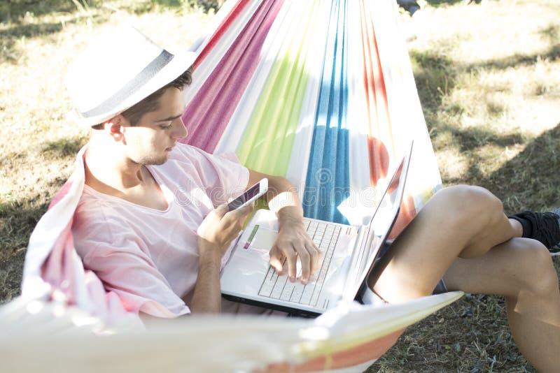 Giovani con il computer portatile nell'amaca, estate fotografie stock