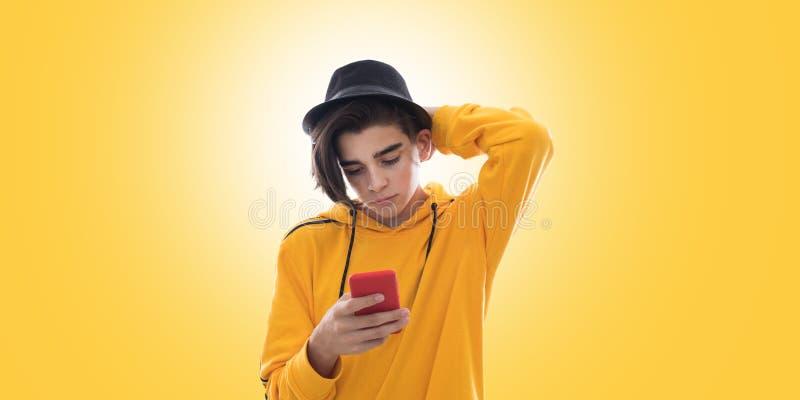 Giovani con il telefono cellulare da adattare su giallo fotografia stock