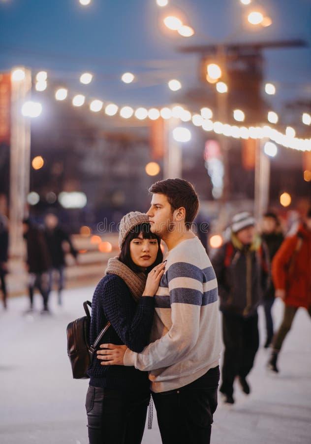 Giovani coppia in piedi e abbracci sul fondo delle luci della città immagine stock libera da diritti