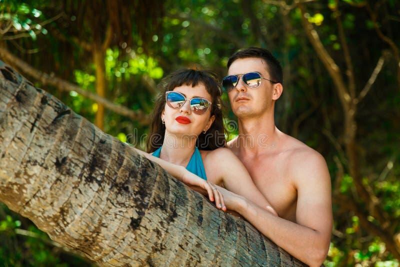Giovani coppie accanto ad una palma nella giungla su un isl tropicale immagine stock