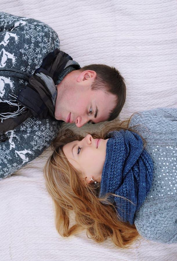 Giovani coppie adorabili che si trovano in un letto, sorriso felice che guarda l'un l'altro immagine stock libera da diritti