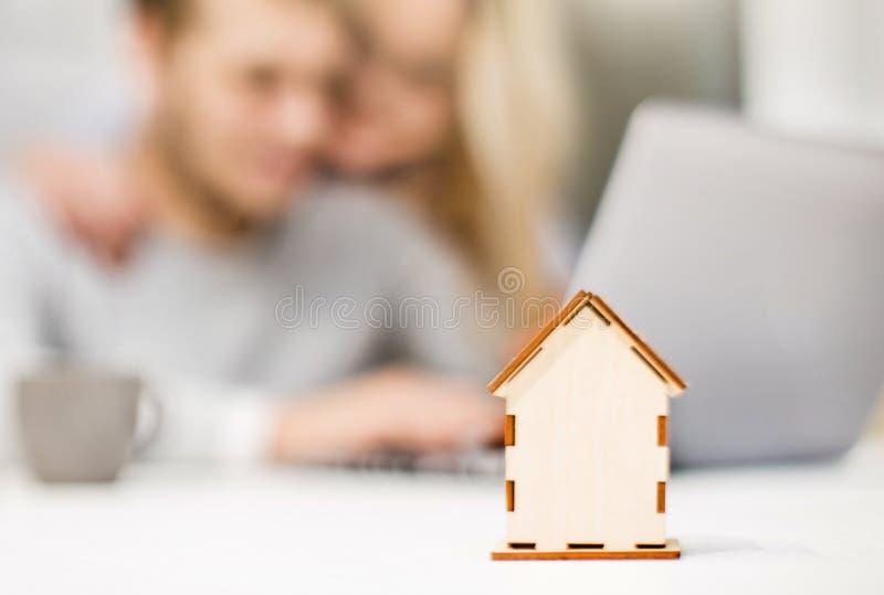 Giovani coppie adorabili, facendo uso di un computer portatile e della scelta dell'appartamento nuovo Disposizione della casa nel fotografia stock