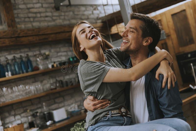 Giovani coppie adorabili felici nella cucina che si abbraccia immagini stock