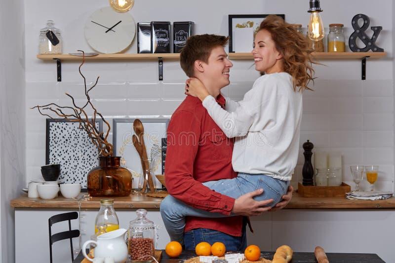 Giovani coppie adorabili felici sulla cucina che si abbraccia Godono di di spendere il tempo insieme fotografia stock libera da diritti