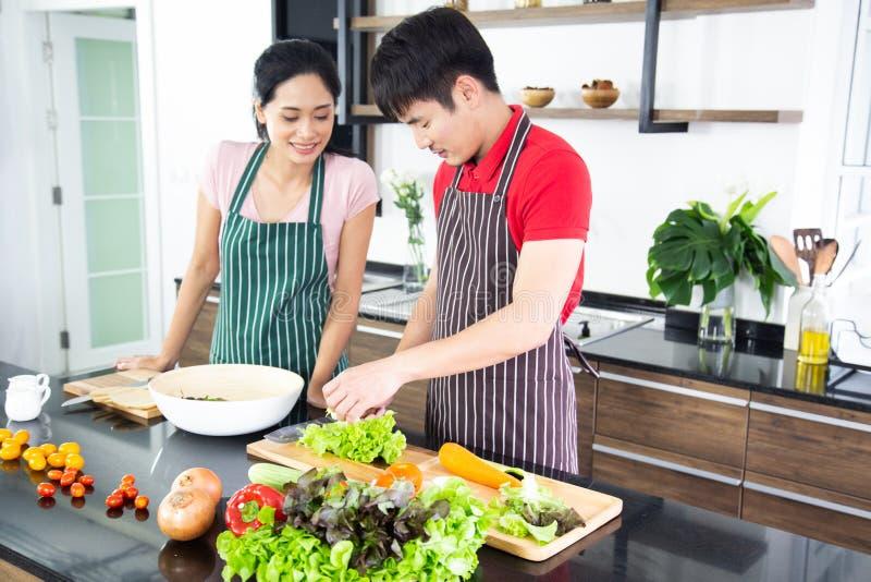 Giovani coppie adorabili romantiche che cucinano alimento nella cucina fotografie stock