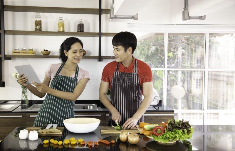 Giovani coppie adorabili romantiche che cucinano alimento nella cucina fotografia stock