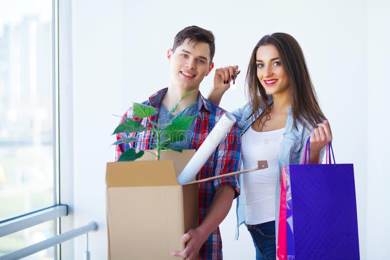 Giovani coppie adulte dentro stanza con le scatole che tengono le chiavi della nuova casa immagine stock libera da diritti