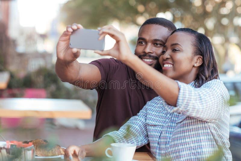 Giovani coppie africane che prendono i selfies ad un caffè del marciapiede fotografie stock