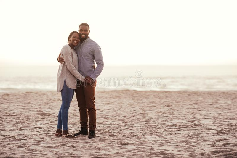 Giovani coppie africane sorridenti che stanno su una spiaggia al tramonto fotografia stock