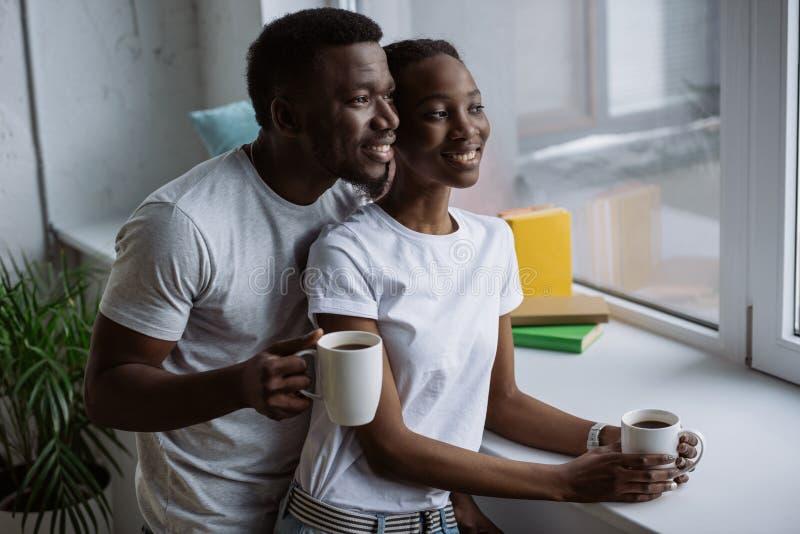 giovani coppie afroamericane felici che tengono le tazze di caffè e sguardo immagine stock