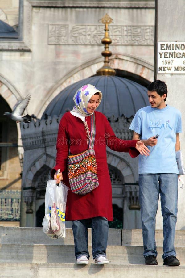 Giovani coppie all'entrata di nuova moschea Yeni Cami a COSTANTINOPOLI, TURCHIA fotografie stock