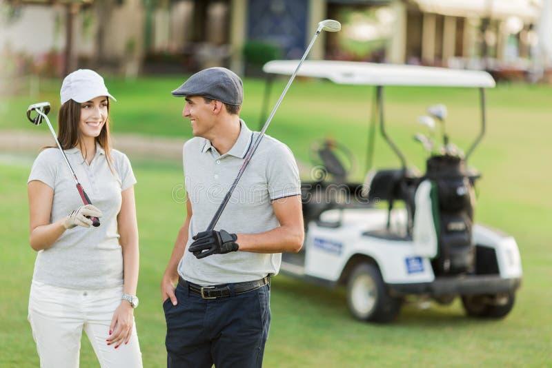 Giovani coppie alla corte di golf fotografia stock