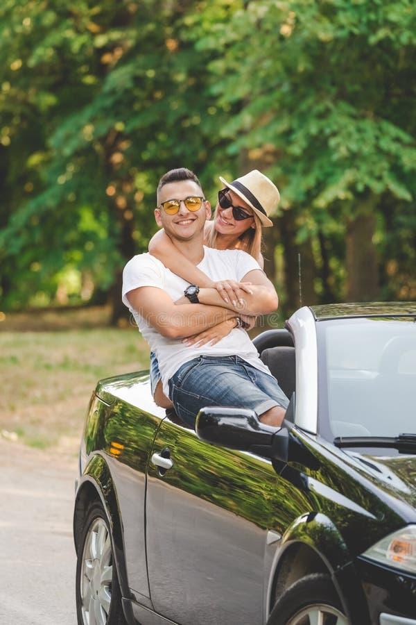 Giovani coppie alla moda in automobile del cabriolet in natura Sul concetto di vacanze estive di viaggio stradale fotografia stock libera da diritti