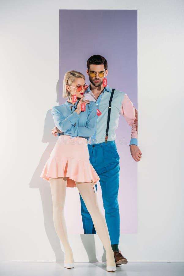 giovani coppie alla moda con le etichette di vendita sui vestiti che stanno nell'apertura fotografia stock