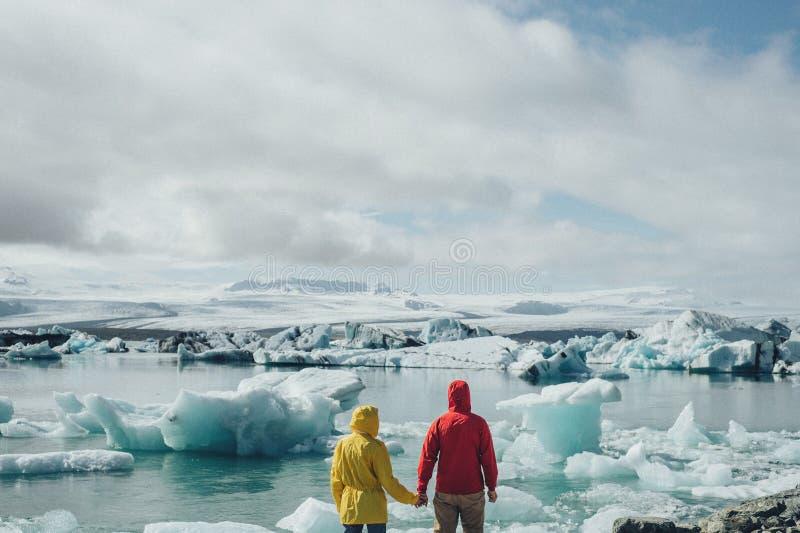 Giovani coppie alla moda in Islanda vicino alla laguna glaciale immagini stock libere da diritti
