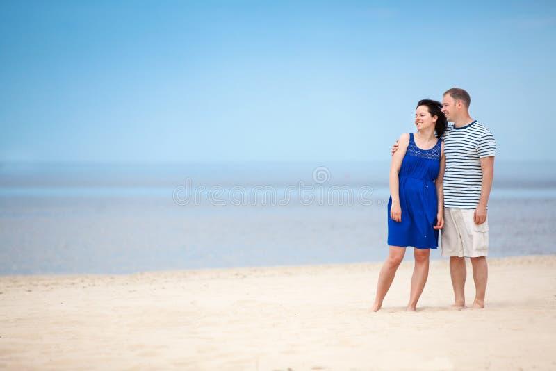 Giovani coppie alla spiaggia tropicale sulle vacanze estive fotografie stock libere da diritti