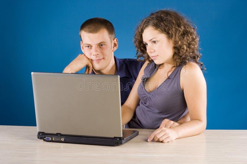 Giovani coppie alla tabella con il computer portatile immagini stock libere da diritti