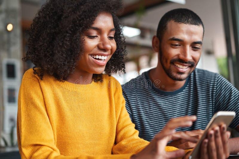 Giovani coppie allegre che esaminano smartphone fotografie stock libere da diritti
