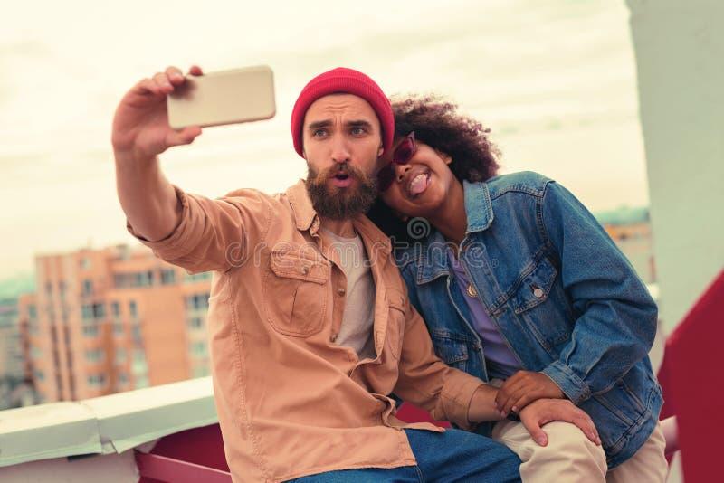 Giovani coppie allegre che fanno i fronti sciocchi mentre prendendo i selfies immagine stock