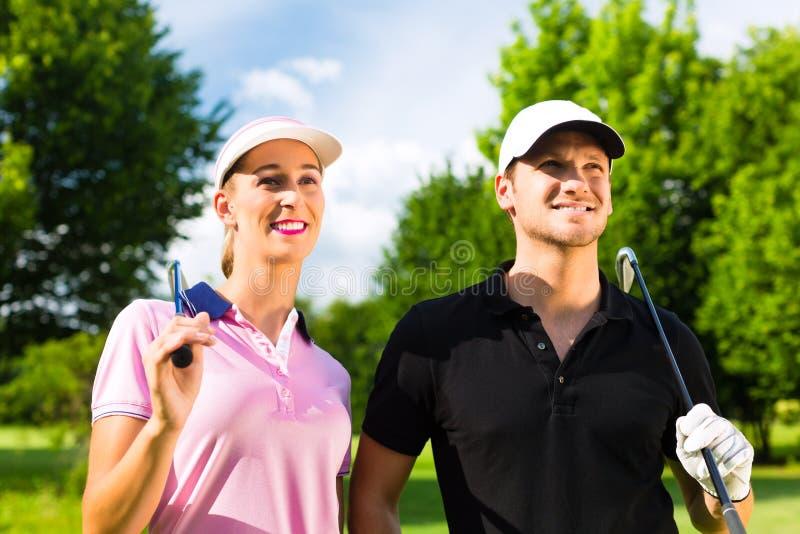 Giovani coppie allegre che giocano golf su un corso immagini stock