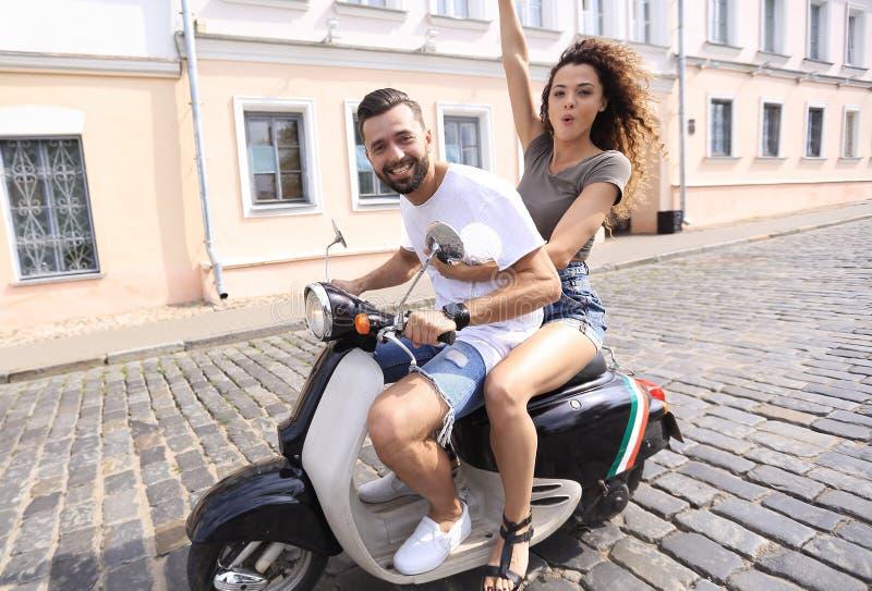 Giovani coppie allegre che guidano un motorino e divertiresi fotografia stock libera da diritti