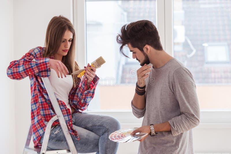 Giovani coppie allegre che scelgono colore per la casa di verniciatura fotografia stock libera da diritti