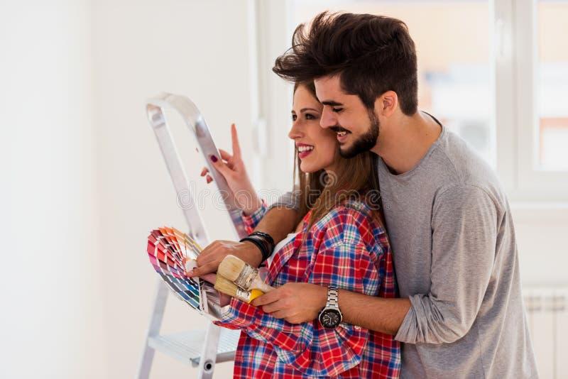 Giovani coppie allegre che scelgono colore per la casa di verniciatura fotografia stock