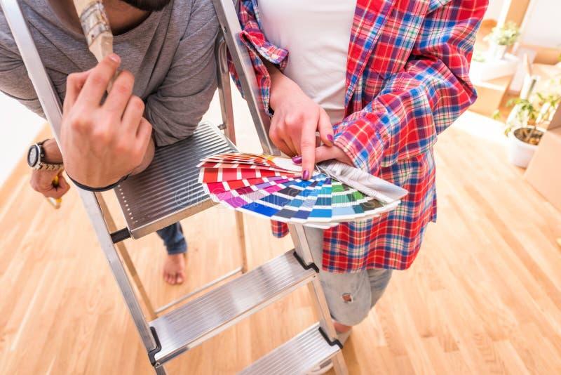 Giovani coppie allegre che scelgono colore per la casa di verniciatura immagini stock libere da diritti