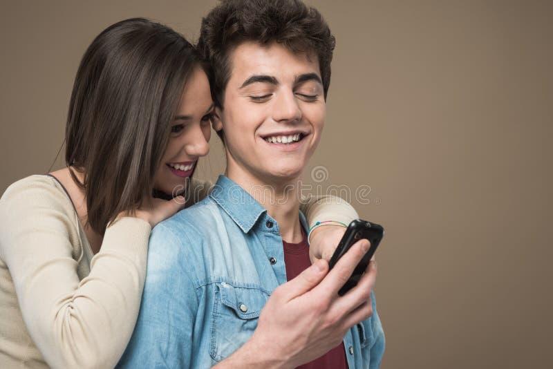 Giovani coppie allegre con il telefono cellulare immagine stock libera da diritti