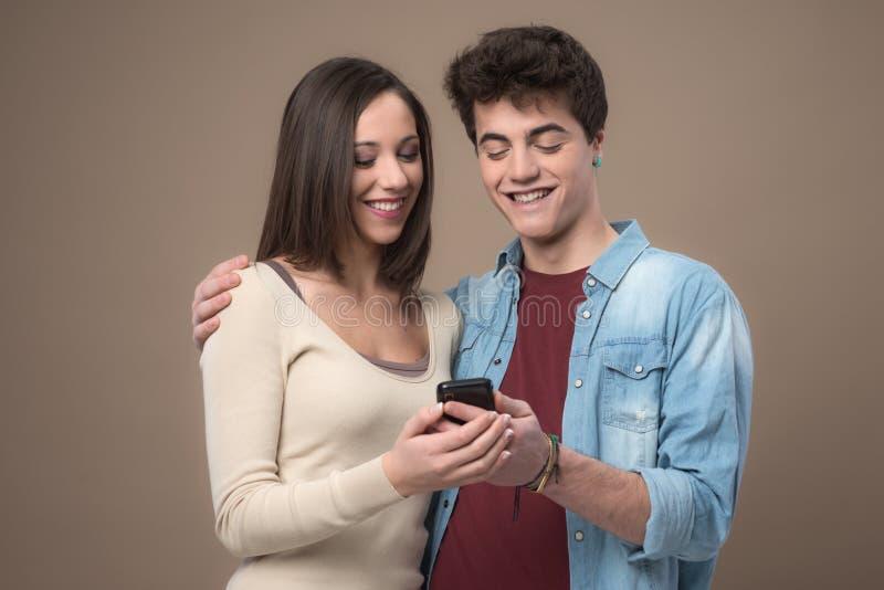 Giovani coppie allegre con il telefono cellulare fotografia stock