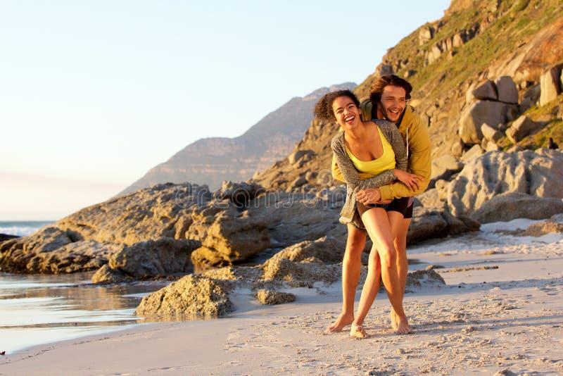 Giovani coppie allegre della corsa mista alla spiaggia fotografie stock