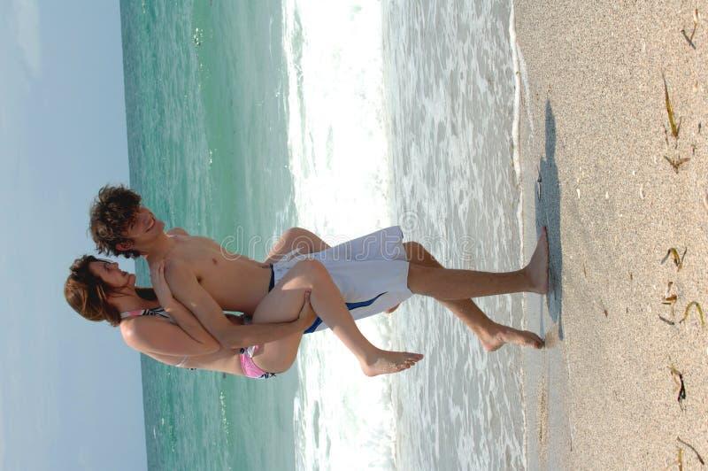 Giovani coppie allegre della spiaggia fotografie stock