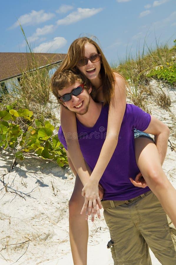 Giovani coppie allegre della spiaggia immagine stock libera da diritti