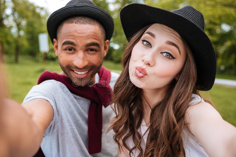 Giovani coppie allegre felici che fanno selfie in parco immagini stock libere da diritti