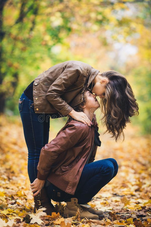 Giovani coppie amorose in autunno in parco La ragazza bacia il tipo in naso immagini stock