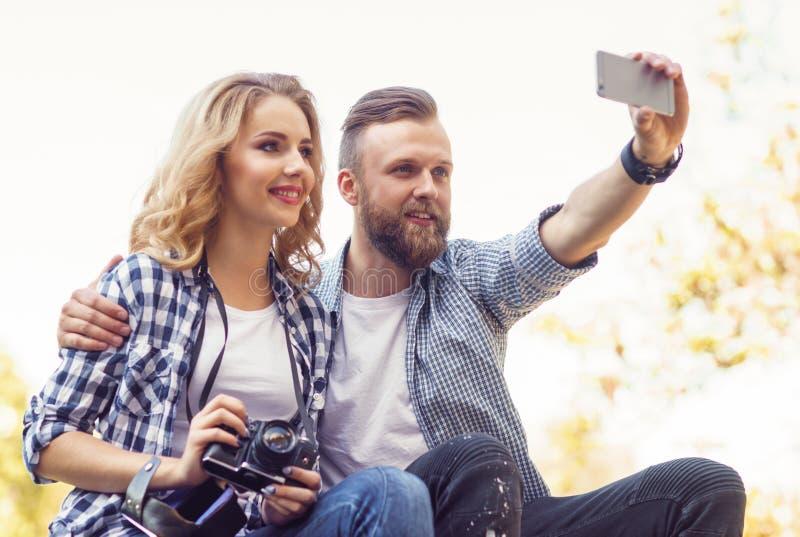Giovani coppie amorose che fanno la foto del selfie nel parco di autunno immagini stock