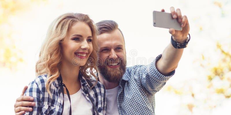 Giovani coppie amorose che fanno la foto del selfie nel parco di autunno immagine stock