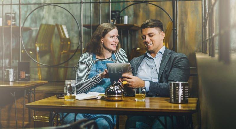 Giovani coppie amorose che si siedono in caffè alla tavola e che per mezzo del computer della compressa La ragazza ed il tipo uti fotografie stock libere da diritti